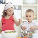 Two cute little children playing in the kitchen preparing salad