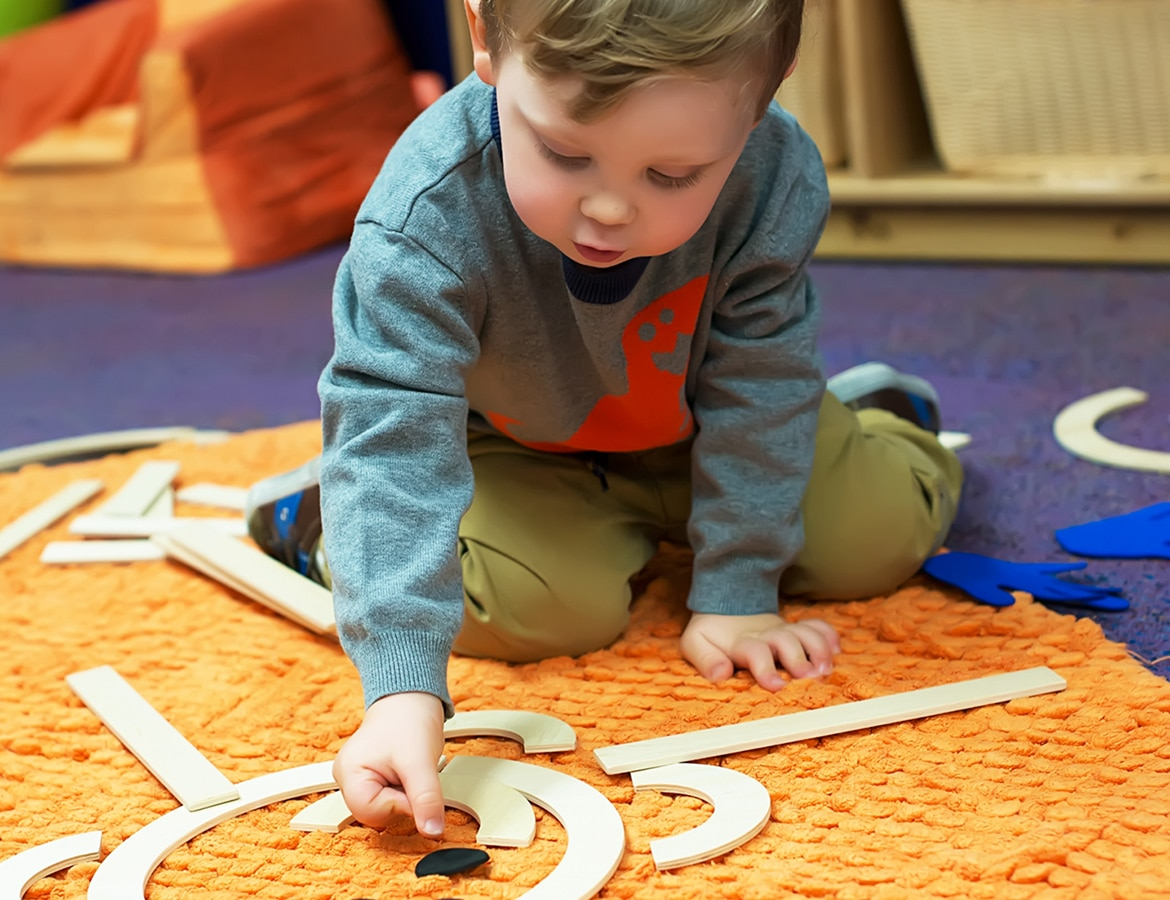Toddler playing on a matt in preschool