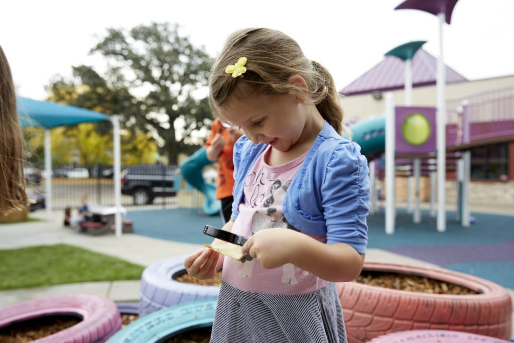 Child on Playground looking through Magnifying Glass